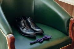 Collage av kläder för ` s för moderna män på grön bakgrund Brudgumdetaljen skor den manliga skor och flugan på den gröna fåtöljen arkivbilder