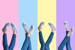 Collage av kvinnlign lägger benen på ryggen i jeans och gymnastikskor på kulör bakgrund arkivfoto