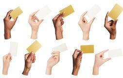 Collage av olika händer som rymmer tomma affärskort som isoleras arkivfoto