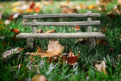 Collage bench in autumn grass. Royalty Free Stock Photos