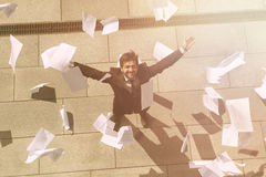 Collage of businessman on street. Collage of businessman or freelance man on street with his arms raised. Many sheets of paper are around him. Office building Royalty Free Stock Photography