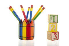 Collage of colorful pencils in a cup next to three 1-2-3 cubes Stock Photo