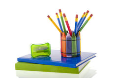 Back to school. A collage of colourfull pencils in a cup with a green pencil sharpener on top of blue and green notebooks, all  over a white background Stock Photos