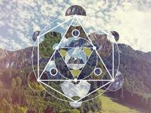 Collage con las montañas y el bosque y el símbolo sagrado de la geometría imagen de archivo