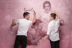 The collage about couple writing something on a pink wall Royalty Free Stock Photos