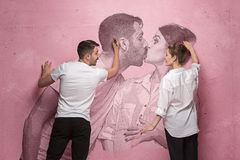 The collage about couple writing something on a pink wall. On the wall my photo of female and male kiss. Concept of love and new family Royalty Free Stock Photo