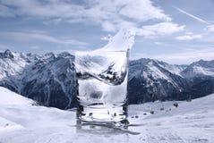 Collage d'un verre avec l'eau et les glaçons clairs avec une éclaboussure et une station de sports d'hiver dans les Alpes Image stock