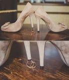 Collage de zapatos nupciales beige con los anillos de bodas Fotografía de archivo