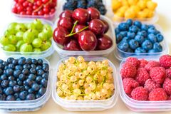 Collage dei frutti differenti e bacche su bianco Mirtilli, ciliege, more, uva, fragole, uva passa Co Fotografie Stock