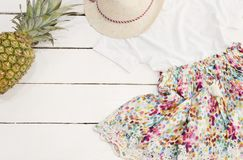 Collage dei vestiti e degli accessori delle ragazze Cappello di paglia, vestito floreale, ananas Vecchio fondo di legno bianco Fotografie Stock