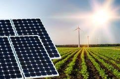 Collage della foto dei pannelli solari e dei turbins del vento contro i precedenti dei raccolti Immagine Stock
