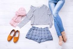 Collage della raccolta dell'abbigliamento del ` s delle donne e delle gambe femminili su fondo di legno bianco Vista superiore Fotografie Stock