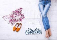 Collage della raccolta dell'abbigliamento del ` s delle donne e delle gambe femminili su fondo di legno bianco Vista superiore Immagine Stock