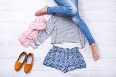 Collage della raccolta dell'abbigliamento del ` s delle donne e delle gambe femminili su fondo di legno bianco Vista superiore Immagine Stock Libera da Diritti
