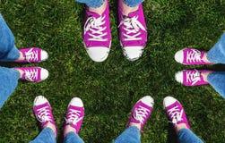 Collage des jambes dans de vieilles espadrilles roses sur l'herbe verte Vue d'a Photo stock