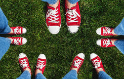 Collage des jambes dans de vieilles espadrilles rouges sur l'herbe verte Vue d'ab Image stock