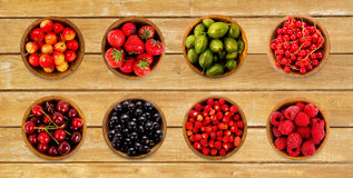 Collage of different fruits and berries  on wooden background. Royalty Free Stock Photos