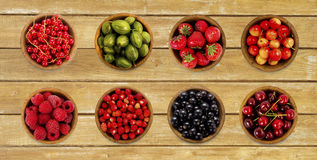 Collage of different fruits and berries on the wooden table. Stock Image