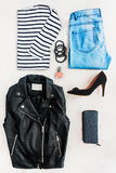 Collage of female clothing set.  Blue jeans, striped blouse, leather jacket, black high heels shoes and accessories over white woo Royalty Free Stock Images