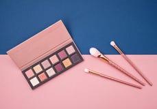 Collage femminile dei cosmetici di disposizione piana con gli ombretti e le spazzole o immagini stock libere da diritti