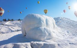 Hot air ballons flying above snowy white Pamukkale in Turkey Royalty Free Stock Photos