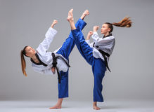 The collage of karate girl with black belt. The collage of karate girl in white kimono and black belt training karate over gray background Stock Photography