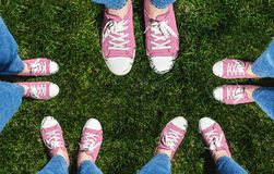 Collage of legs in old pink sneakers on green grass. View from a stock photography