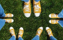 Collage of legs in old yellow sneakers on green grass. View from stock photos