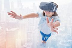 Collage of little girl in VR headset standing atop urban landscape Royalty Free Stock Image