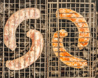 Collage of raw and fried sausages in the grill to cook in the gr stock photo