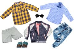 Collage set of children clothes. Denim jeans or pants, shoes, two checkered shirts, rain jacket and shorts for child boy isolated royalty free stock image