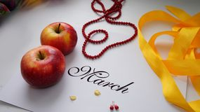 Collage to the international women`s day. Of apples, yellow ribbon, beads, bracelet. March 8 Stock Image