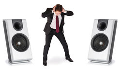 Collage - too loud. Young man in business suit holding his head with hands between two speakers. Isolated on white Royalty Free Stock Photo