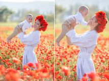 A happy mother with a small son in her arms on the endless field of red poppies on a sunny summer day Stock Photography