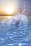 The collage of a woman coming out from the sea at sunset Stock Photo