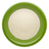 Collagen protein powder. On an isolated green ceramic bowl, top view stock image