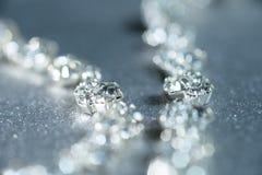 Collana d'argento con il primo piano dei diamanti in defocus su un fondo leggero Immagine Stock