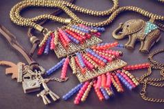 Collana degli accessori nello stile etnico su un fondo nero Sospensione sotto forma di elefante, di pendente colorato multi, un s fotografia stock