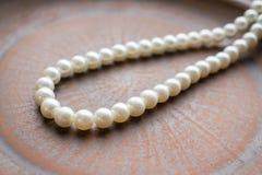 Collana della perla su un piatto marrone dell'argilla Chiuda su del filo di briciolo Immagini Stock