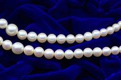 Collana della perla sul panno blu Fotografie Stock Libere da Diritti