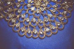 Collana dorata su fondo blu retro Fotografia Stock