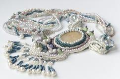 Collana tessuta fatta a mano della perla del seme un fondo bianco Fotografia Stock