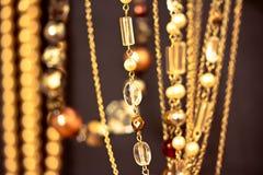 Collane e gemme dorate, dof poco profondo sul nero Immagine Stock
