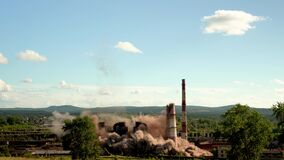 The collapse of an industrial chimney. Explosion of an old chimney of an obsolete metallurgical plant