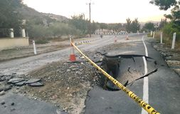 Collapsed asphalt road. Broken road with police sign forbidding the passing royalty free stock images