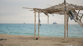 Collapsed awning of bamboo on an abandoned beach. Not the season, ecology concept stock video
