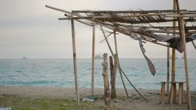 Collapsed awning of bamboo on an abandoned beach. Not the season. ecology concept stock video