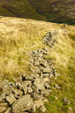 Collapsed Dry Stone Wall. Collapsed stone wall on a hill Royalty Free Stock Photo