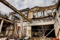 Collapsed factory. Old abandoned and collapsed factory with rubble and debris - ruins of an ancient industrial building - hdr image Royalty Free Stock Image