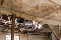 Collapsed roof of the total damaged domestic house indoor from natural disaster or catastrophe. Damaged house. Collapsed roof of the total damaged domestic house Royalty Free Stock Photos